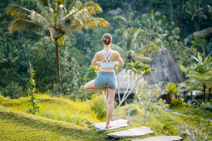 Woman doing yoga in a rainy forest meditating Transcendence Woman Adult Awesome Connected Exercising Forest Healthy Lifestyle Meditating Nature Outdoors Rainforest Relaxation Sport Warrior Pose Wellbeing Women Yoga