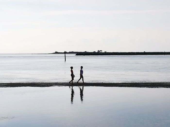 Silhouette friends standing on beach against sky