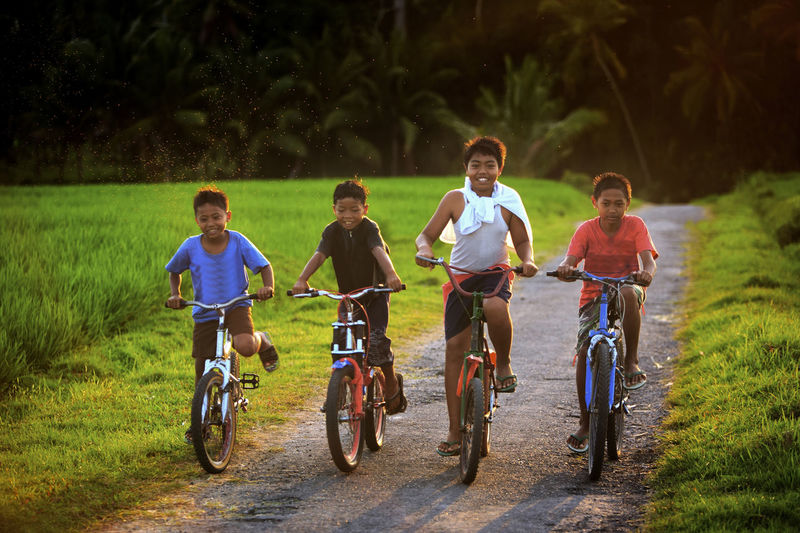 Four boys riding bicycles on dirt road at field
