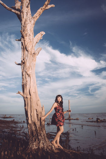 Portrait of young woman standing on tree trunk by sea against sky