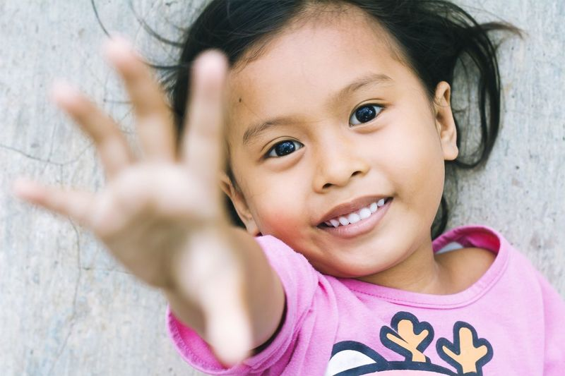 Portrait of cute girl smiling while gesturing by wall