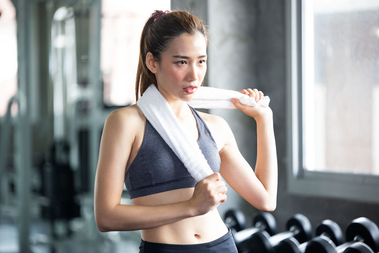 Young woman holding towel while looking away in gym