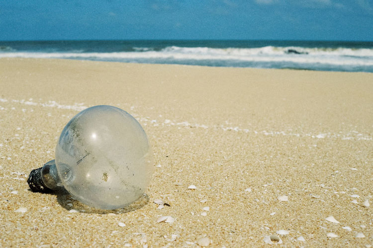 Close-up of light bulb on beach