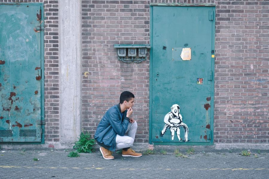 Banksy Rotterdam Adult Adults Only Architecture Building Exterior Built Structure Casual Clothing City Day Full Length Green Door Men Old Architecture One Man Only One Person One Young Man Only Only Men Outdoors People Real People Sitting Timberlands Urban Young Adult