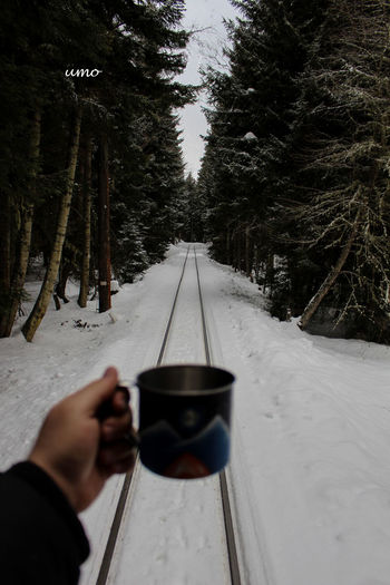 Hand Holding Cup Over Railroad Tracks During Winter
