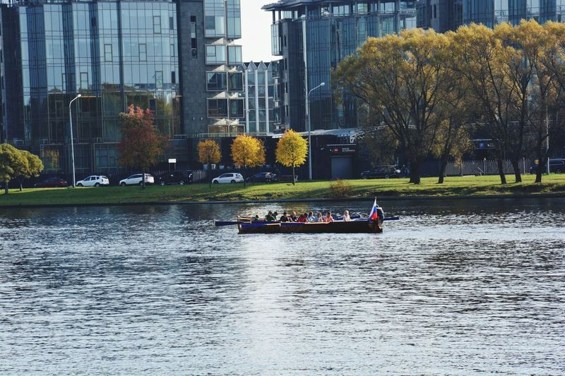 People on river by trees in city