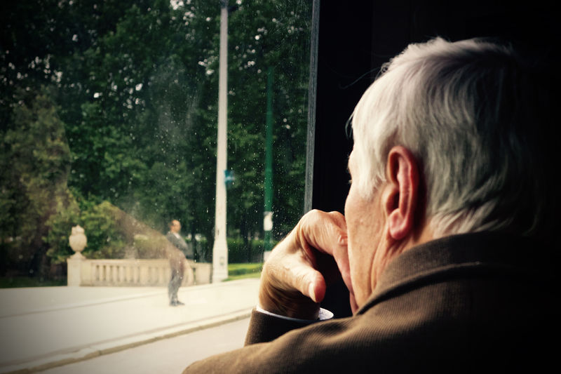 Close-up of senior man looking through window