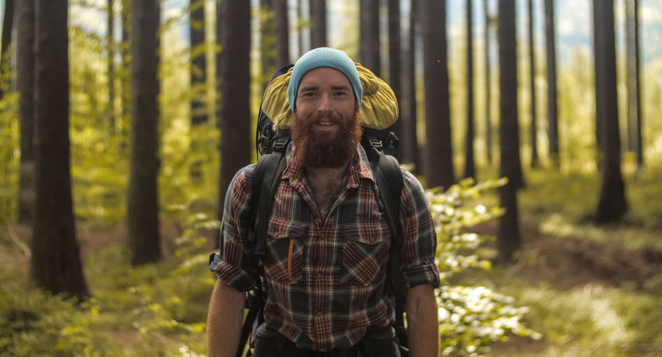 portrait of a caucasian male hiker standing outdoors in a forest with a backpack Camping Hiking Man Nature Plaid Shirt  Travel Trekking Wood Youth Adventure Bald Beard Caucasian Forest Ginger Headshot Lumberjack Male One Person Outdoors Outside Portrait Young Adult
