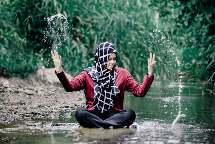 One Person Water Nature Sitting Plant Clothing Young Adult Happiness Lifestyles Arms Raised Outdoors Woman In Hijab Water Splash Stream Flowing Water Rainforest Leisure Activity Nature Games International Women's Day 2019