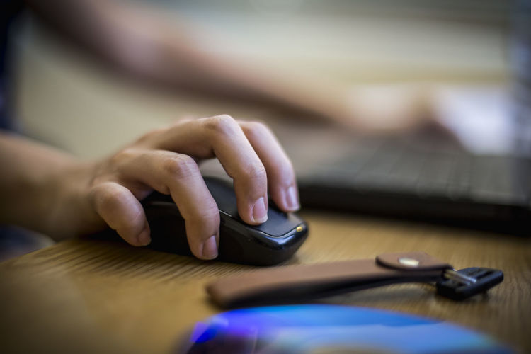 Cropped Hand Of Person Holding Computer Mouse By Key On Desk