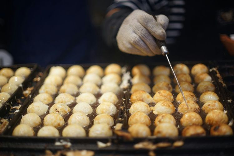 Cropped Image Of Vendor Preparing Takoyaki At Stall