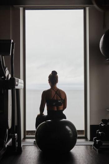 Rear view of woman sitting on window