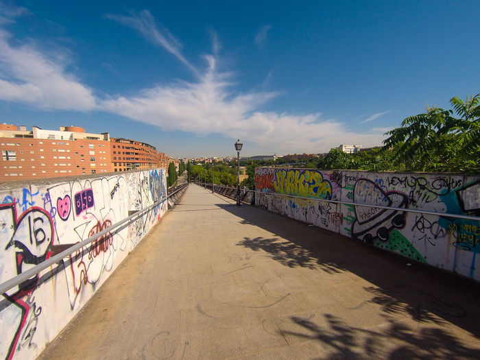 Graffiti on wall by footpath against sky in city