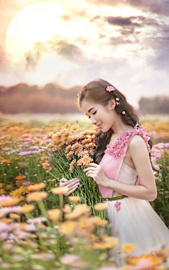 Young woman with pink flowers against sky during sunset