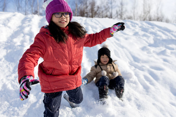 Siblings playing in snow during winter