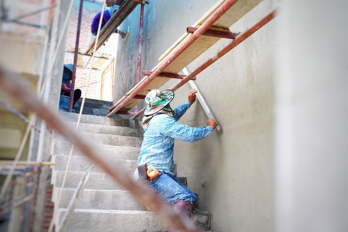 Workers plastering the cement texture on the brickwork wall by using trowel at the house under construction. Scaffolding Steel Engneering Construction Stair Flat Smoothness Skill  Trowel Plastering Wall Building Wall - Building Feature Architecture Built Structure Lifestyles Real People Day Full Length People Building Exterior Outdoors Sunlight Hanging