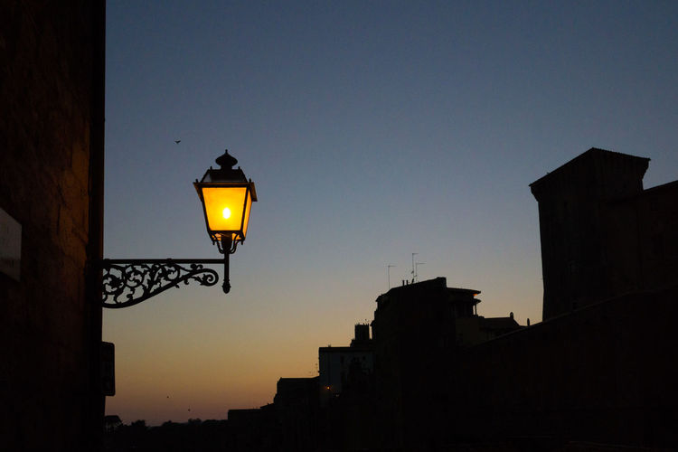 Low angle view of illuminated street light against buildings at dusk