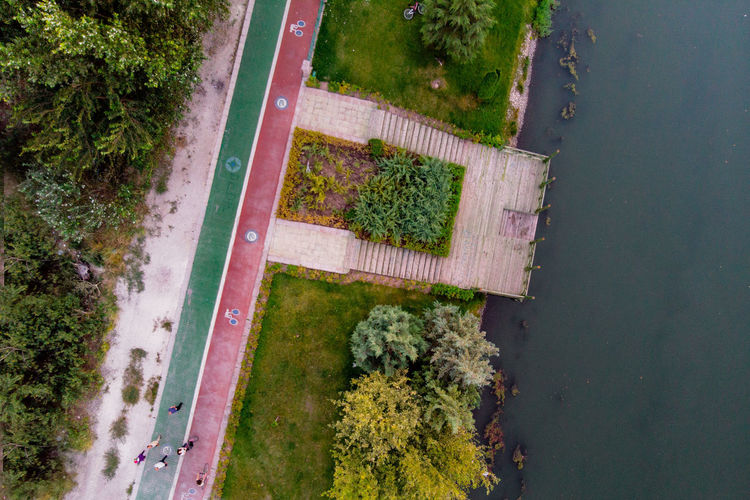 Top view of the pier and walking path. Plant No People Day Nature Green Color High Angle View Water Tree Growth Outdoors Road Tranquility Transportation Beauty In Nature Grass Reflection Directly Above Street Aerial View Hedge Dronephotography Top View Cycling Path Walkway