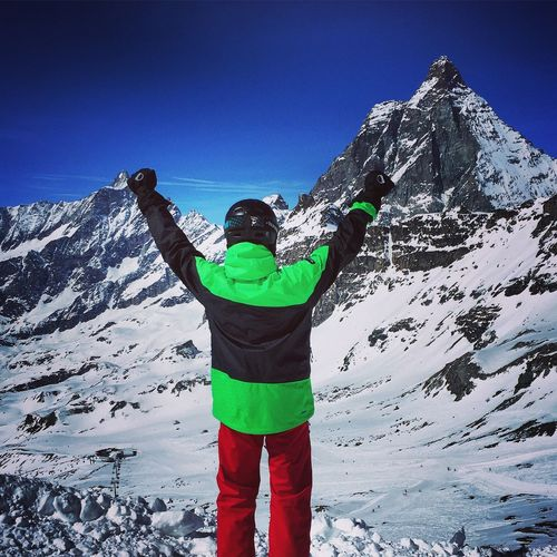 Rear View Of Man With Arms Raised Standing Against Snowcapped Mountains