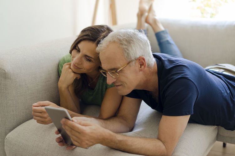 Rear view of man using mobile phone on sofa