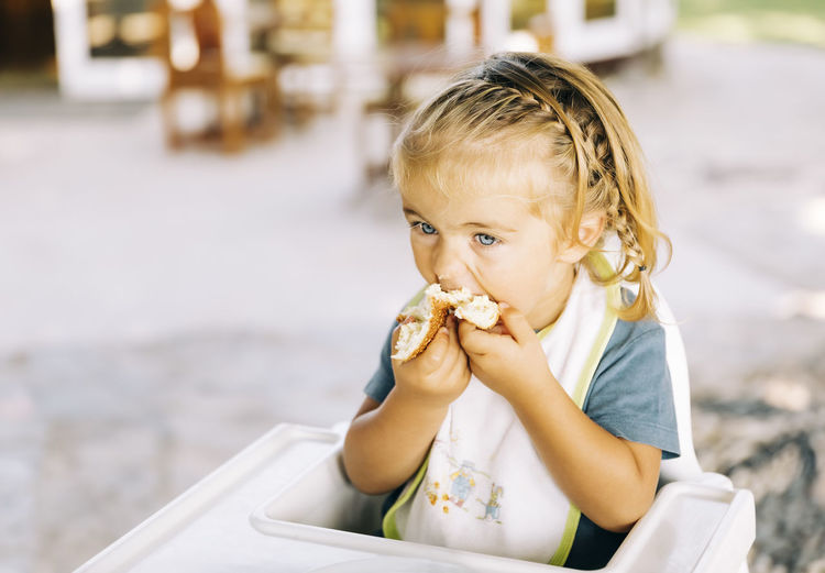 High angle view of girl eating food while sitting on high chair