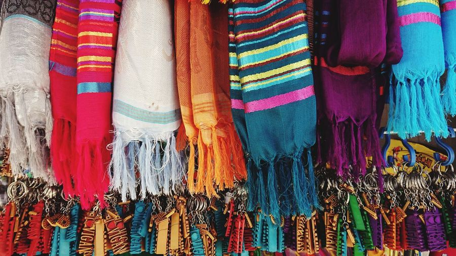Close-up of multi colored scarves hanging at market stall