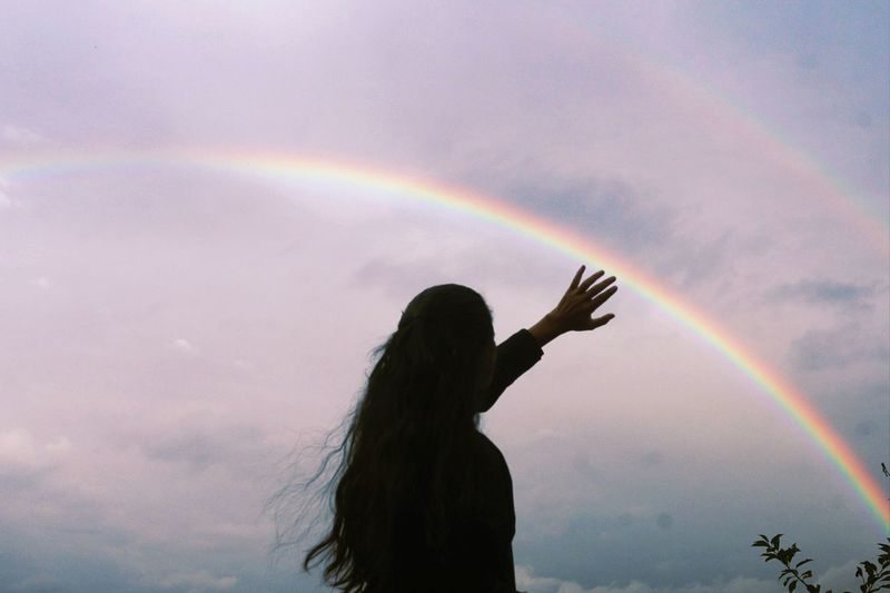 Woman standing against rainbow in sky