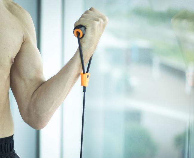 Shirtless man exercising by window