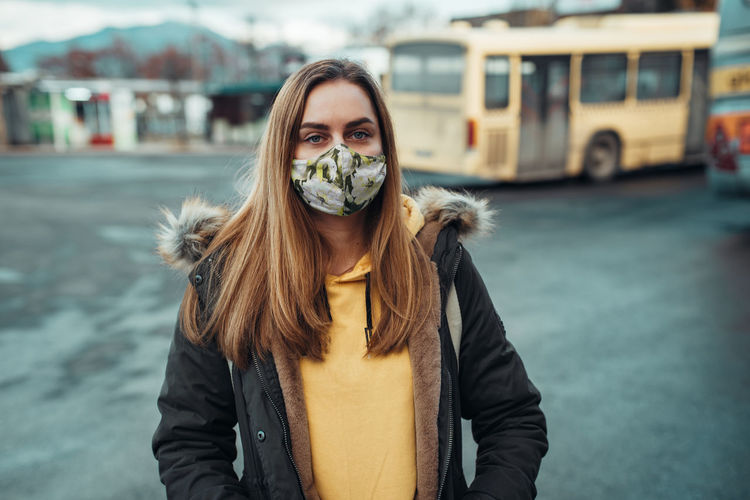 Portrait of young woman standing in city during winter