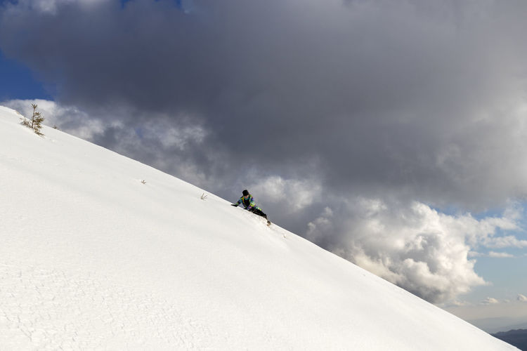 People on snowcapped mountain against sky