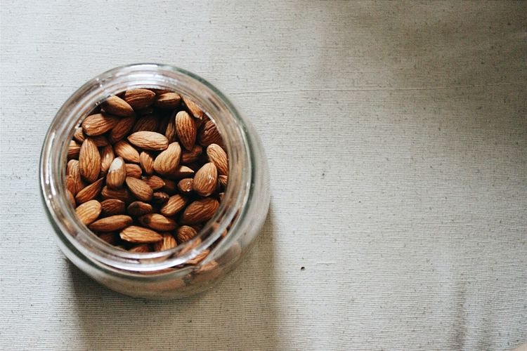 Directly above shot of almonds in glass jar on table
