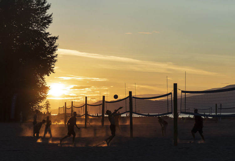 Silhouette people playing beach volleyball against sky during sunset