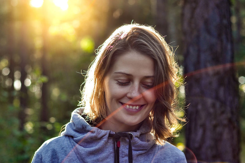 Beautiful Woman Brown Hair Casual Clothing Day Emotion Focus On Foreground Front View Hair Hairstyle Happiness Headshot Leisure Activity Lifestyles Nature One Person Outdoors Portrait Real People Smiling Sunlight Tree Women Young Women