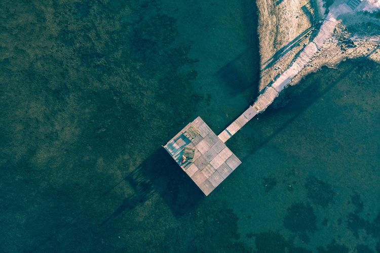 Aerial view of pier on the seaside. Sailboat Copy Space Sunlight Turquoise Colored Coastline High Angle View Land Aerial View Beach Travel Outdoors Day Mode Of Transportation Nautical Vessel Transportation Nature No People Sea Water Directly Above