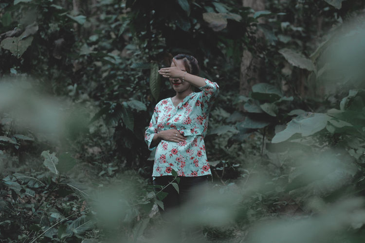 Smiling woman hiding eyes while standing in forest