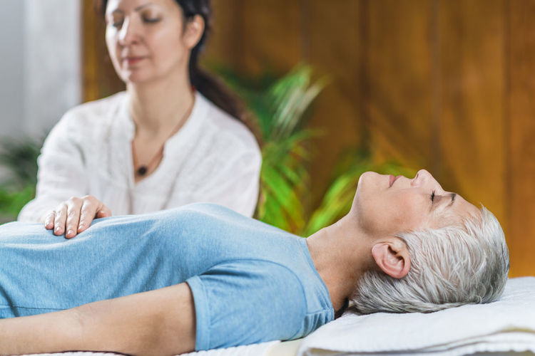 Woman giving massage to client at spa