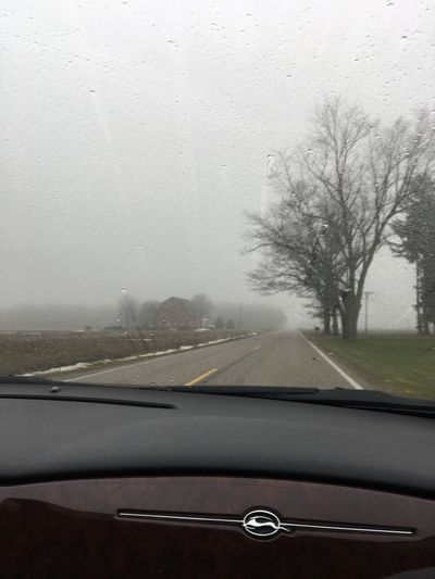 Road seen through wet window during rainy season