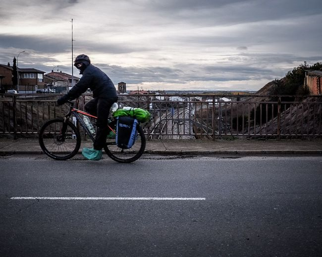 Man riding bicycle on road in city against sky