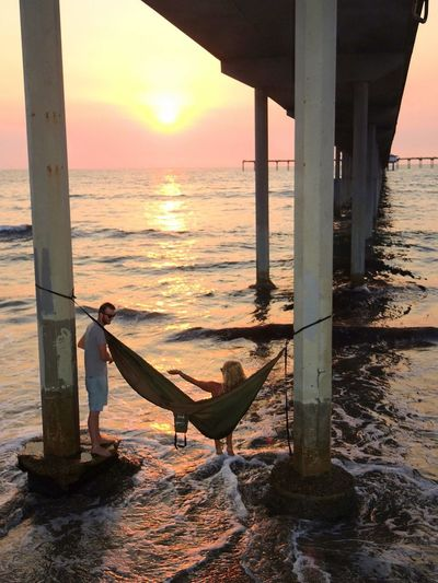 Beach Life Hanging Out Hanging Out With Friends Ocean View Pier Barefoot Lifestyle Beach Fun Cool Breeze Couple - Relationship Day Hammock Heaven Hammock Time Hammocking Hanging Around Lifestyles Nature Outdoors Real People Sunset #sun #clouds #skylovers #sky #nature #beautifulinnature #naturalbeauty #photography #landscape Under The Pier