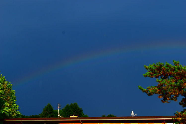 Low angle view of rainbow against blue sky
