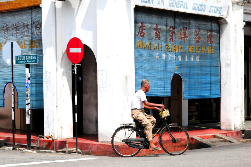 Georgetown Penang Malaysia Photography Malaysia Truly Asia Adult Architecture Bicycle Building Exterior Built Structure City Culture Penang Day Full Length Lifestyles Malaysia Scenery One Person Outdoors People Real People Street Street Corner Penang Street Scene Penang Transportation