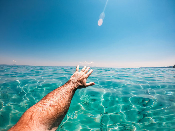 Close-up of man swimming in sea against sky