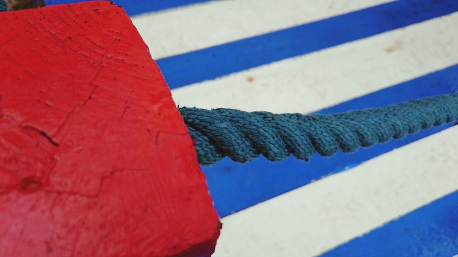 Close-up of blue rope attached to red stone