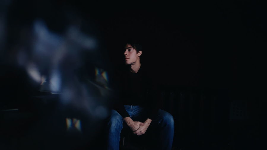 Thoughtful young man looking away while sitting on chair in darkroom