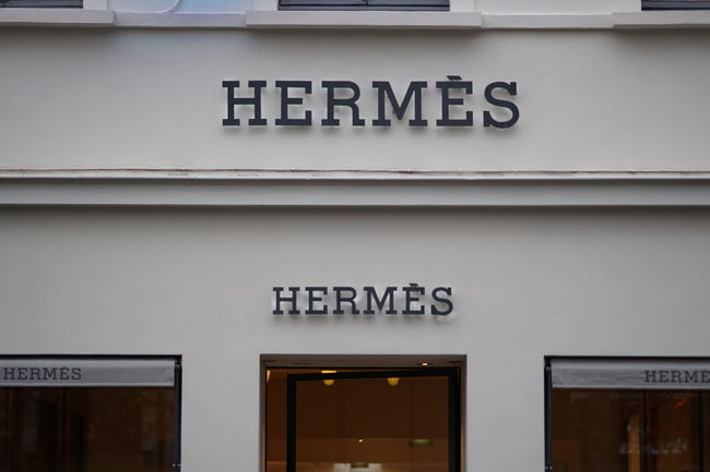 Bruxelles, Belgium - December 9, 2017: Hermes sign. The French high fashion luxury goods manufacturer is specialized in leather, lifestyle accessories, perfumery, jewelry and ready-to-wear Clothes Store Fashion Hermes Brand Building Exterior Business Clothes Shop Clothes Shopping Clothing Shop Clothing Store Editorial  Façade Nameplate No People Outdoors Style