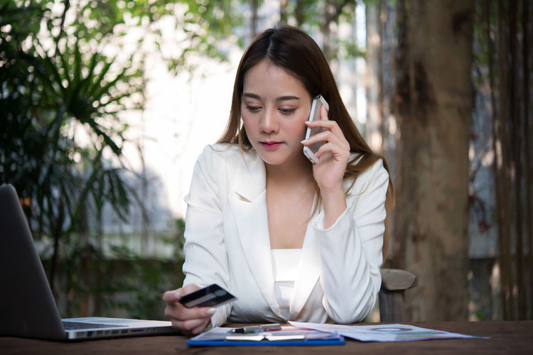 Young woman talking on mobile phone while holding credit card at table