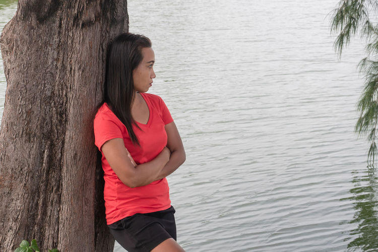 Young woman standing on tree trunk by lake