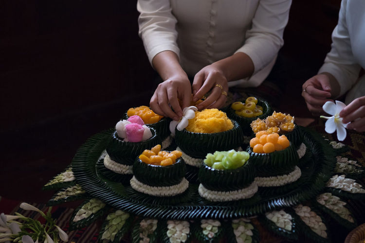 Midsection Of Women Arranging Flowers On Food At Restaurant
