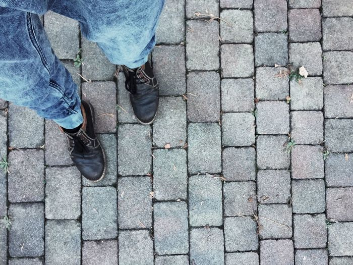 Low section of man standing on paved footpath