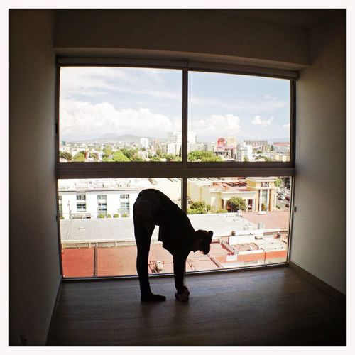 A woman doing Pilates exercises in her modern high rise building. Woman Exercise Pilates Gym Pilates Ball Stretching Window Cityscape Mexico City Fitness